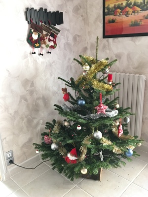 Small decorated Christmas tree and three stockings hung on a coat rack above it